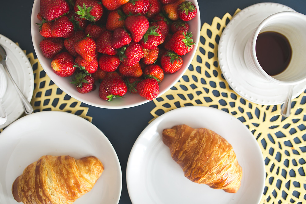 Bowl of strawberries, two small plates with two mini croissants, a mug of black coffee
