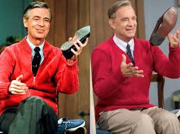 Tom Hanks and Mr. Rogers changing shoes, and wearing the classic red sweater.