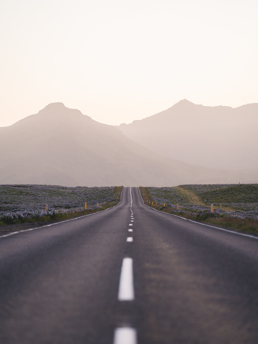 long lonely road in the desert with mountains on the horizon.