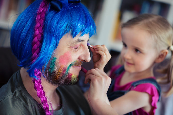Girl applying make up on a man's face