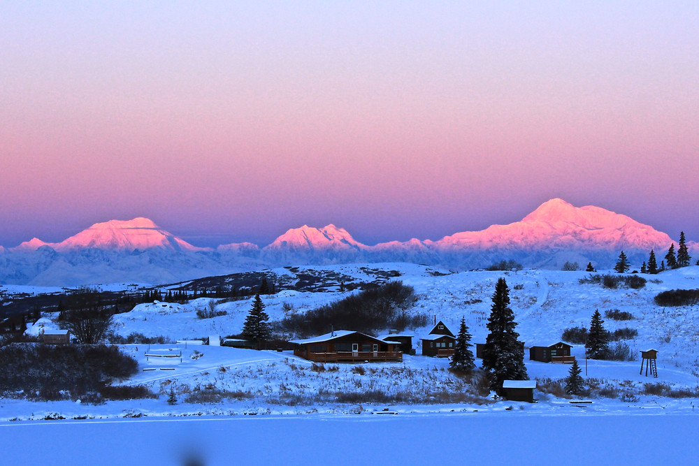 Alpenglow consumes Mt. Foraker, Mt. Hunter & Denali on a cold winter morning, with Caribou Lodge in the foreground.