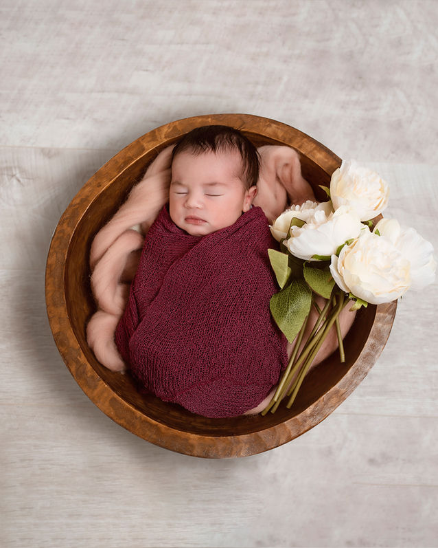 Baby sleeping in wooden bowl