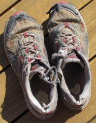 A pair of beat-up, old and worn running shoes