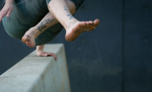The feet and lower body of a person vaulting over a concrete obstacle.