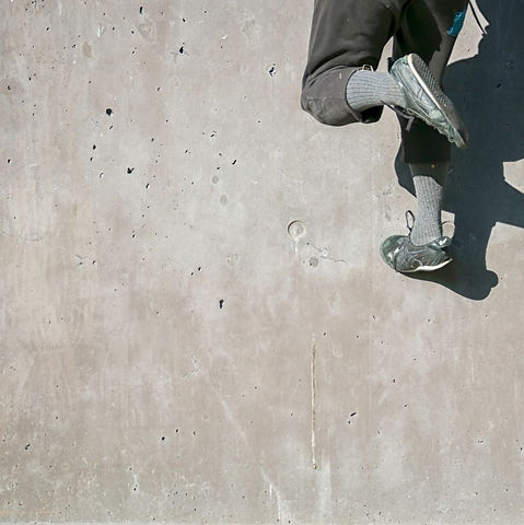 The feet of a person who is part-way through running up a wall