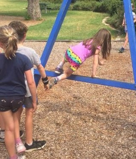 A group of children playing in a playground, with their backs to the camera.