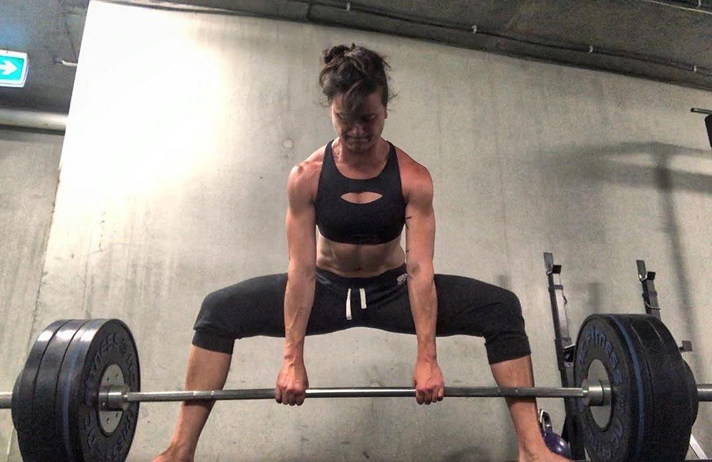 A woman in black trackpants and a black crop top, doing a sumo deadlift.