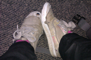 A point-of-view photo of old and worn running shoes on feet.