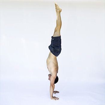 A man in a gynmastic handstand, with toes pointed and straight alignment from wrists to toes. He is shirtless and wearing dark shorts.
