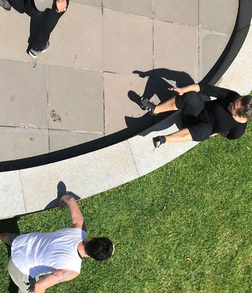 A picture taken from above of two people moving over a small stone wall