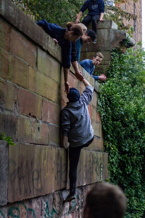 Several people climbing on an old stone wall.