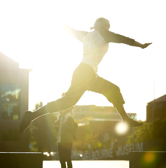 A woman jumping between two concrete blocks. It's sunset and the sun is setting behind her.
