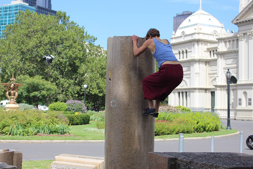 Bri, a tall and athletic woman, climbing a broken marble column, in front of Melbourne's Exhibition Building. It is a bright sunny day.