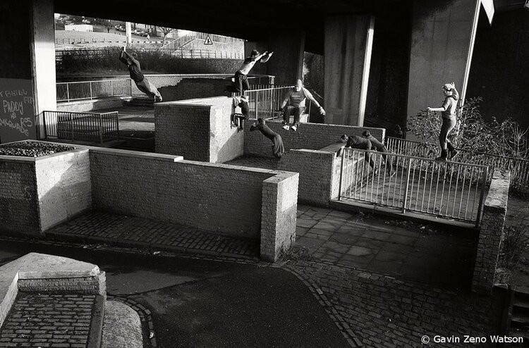 A black and white photo of several people training parkour