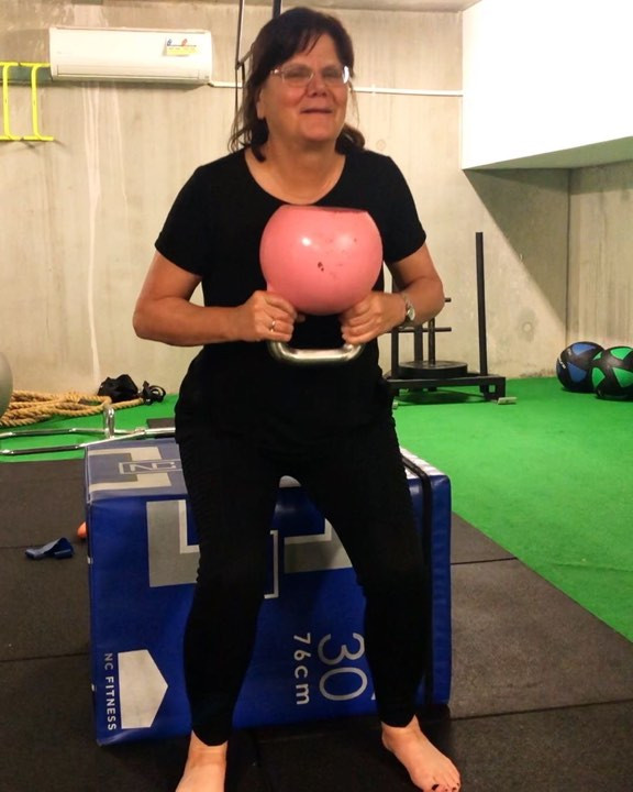 An older woman in black activewear holds a pink kettlebell. She is doing box squats onto a blue plyo box behind her.