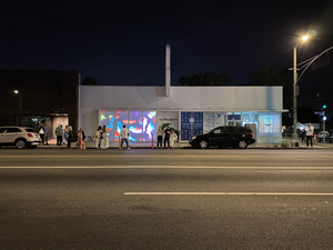 A small gathering of people stand in front of a building with a slideshow in the windows.