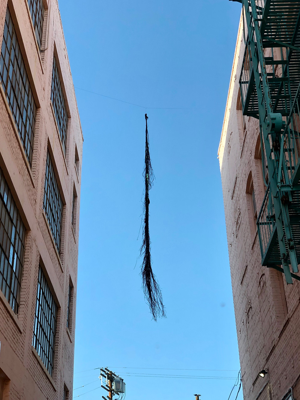 Black material floats between two buildings.