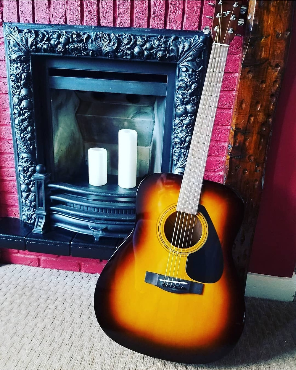 Acoustic guitar beside fireplace