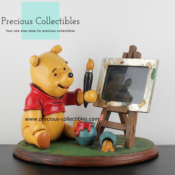 Winnie the Pooh statue and picture frame