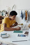 boy-wearing-yellow-shirt-while-writing-o
