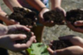 Students holding soil for new seedlings
