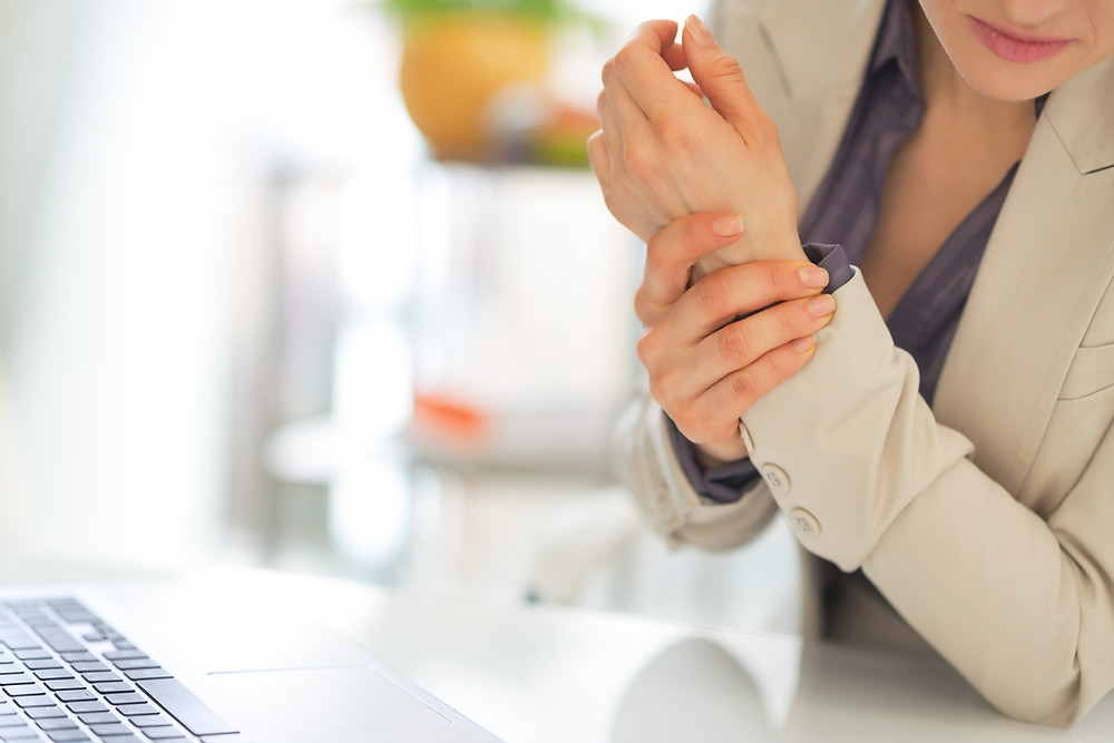 Woman with tendonitis holding her painful wrist