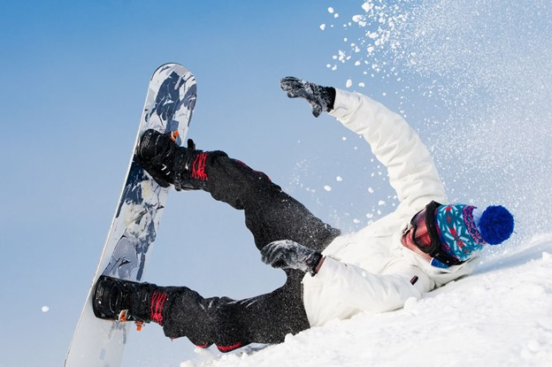 Snowboarder falling and injuring himself