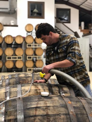 Our assistant winemaker filling barrels