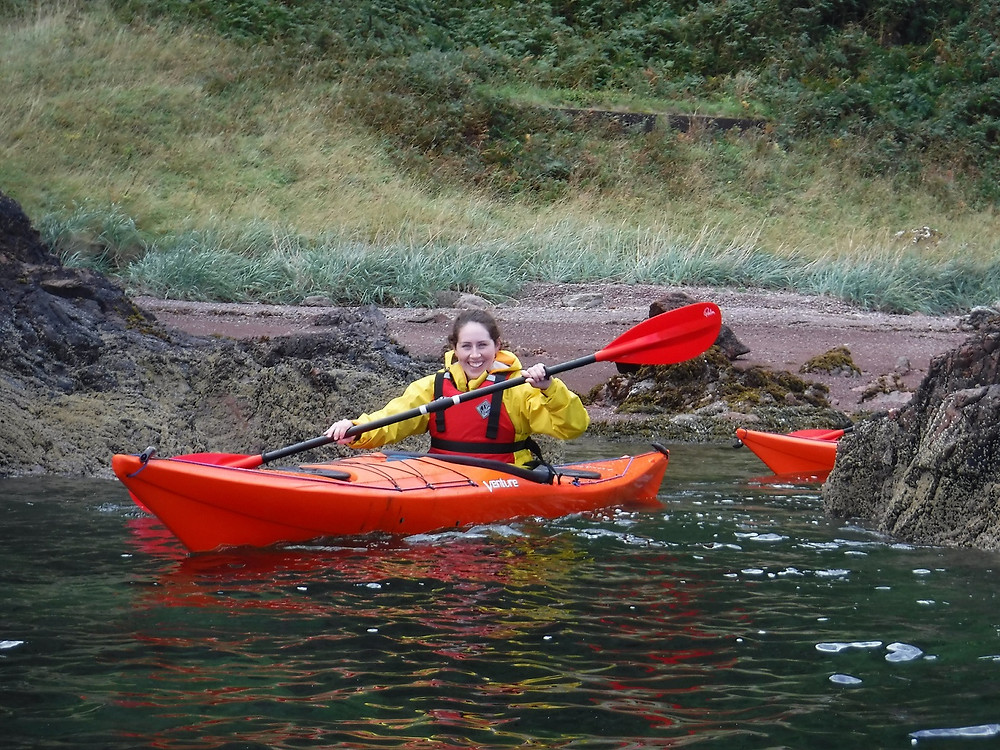 A smiling sea kayaker paddling between the rocks along the shoreline in Scotland.