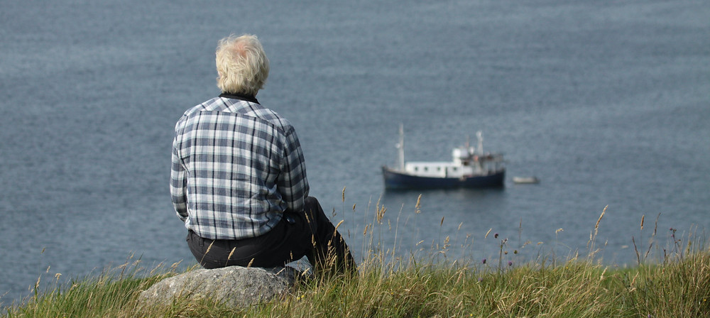 A person sitting on top of a grassy hill on the Shiant Isles looking at the sea.