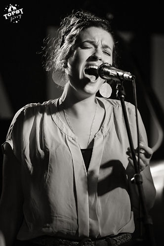 Emily Cooper singing into a microphone