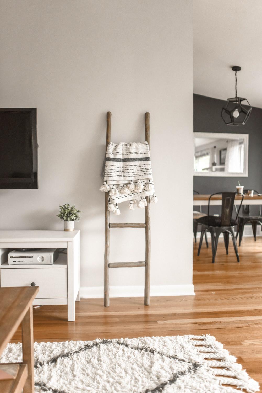 Ambiente limpo e organizado onde se vê parte de um living e, aos fundos, uma sala de jantar. O piso é de madeira.
