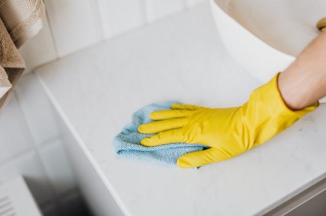 Pessoa vestindo luva amarela de látex usa pano azul claro de microfibra para higienizar bancada de pia.