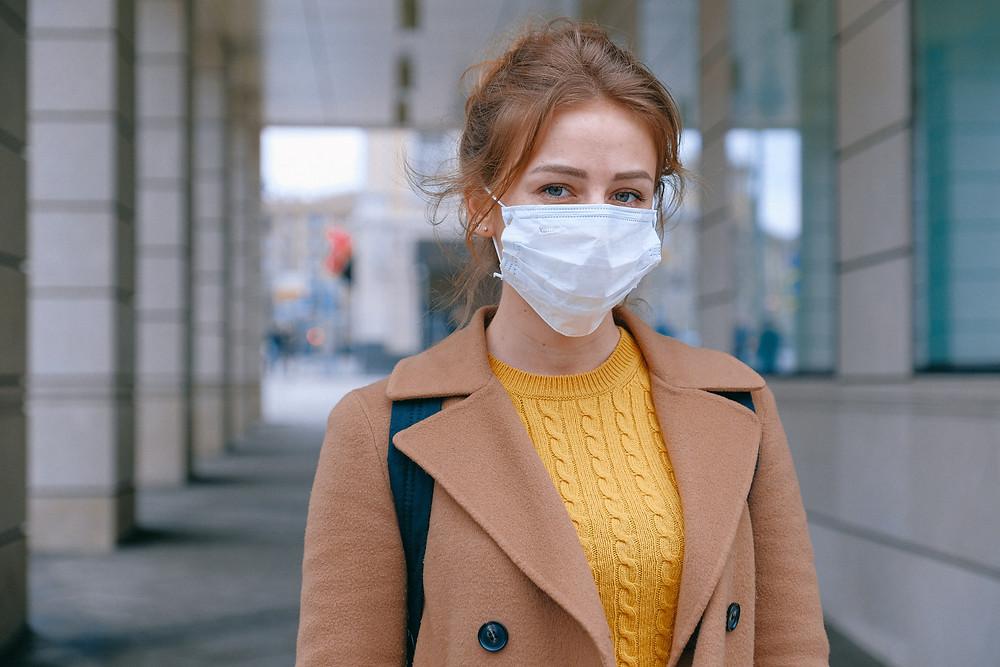 Mulher branca de cabelos claros olha para a câmera enquanto usa máscara cirúrgica no rosto, casaco bege e blusa de tricô amarela. Ela está parada em uma calçada que aparece ao fundo.