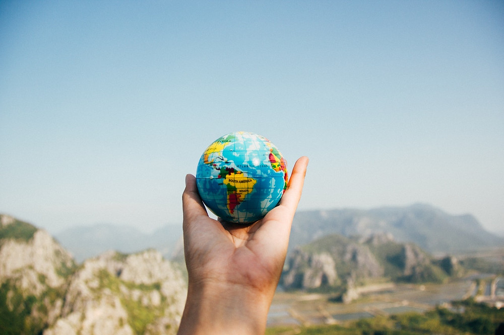 Pessoa segura uma miniatura do globo terrestre em frente a uma paisagem