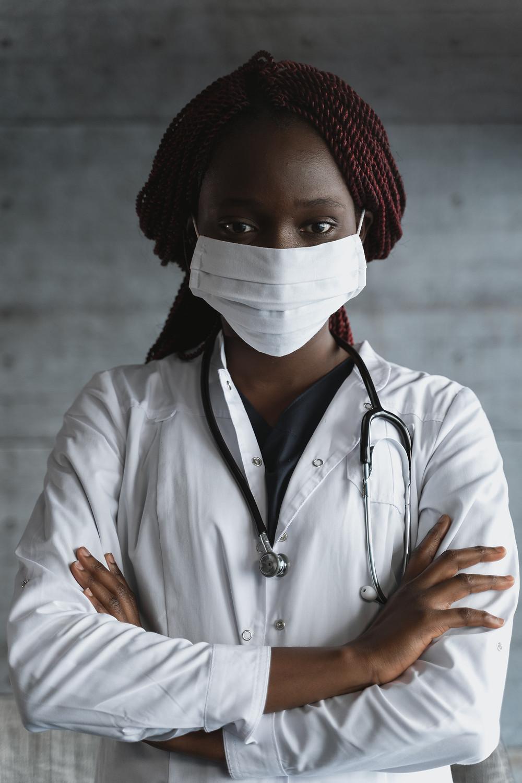 Mulher negra usando máscara cirúrgica em fundo cinza está de braços cruzados, olhando para a câmera e vestindo jaleco médico e possui um estetoscópio no pescoço.