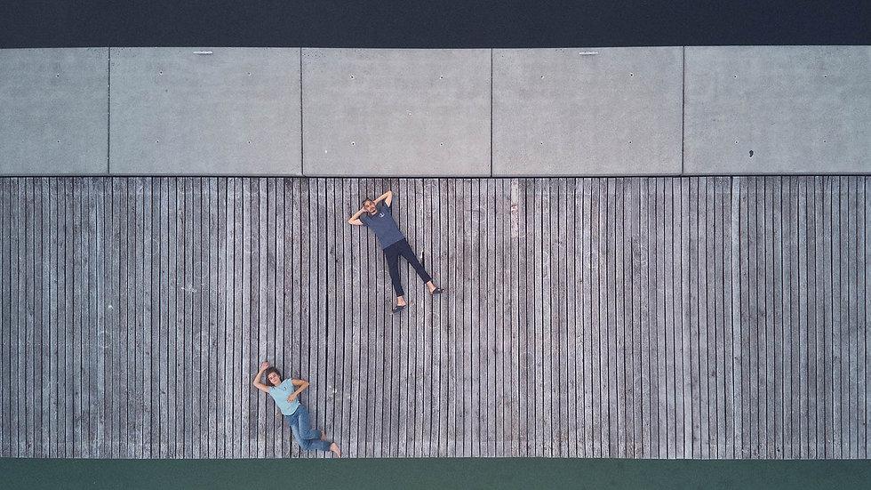 Une homme et une femme couchés sur un ponton et portant des vêtements en coton biologique