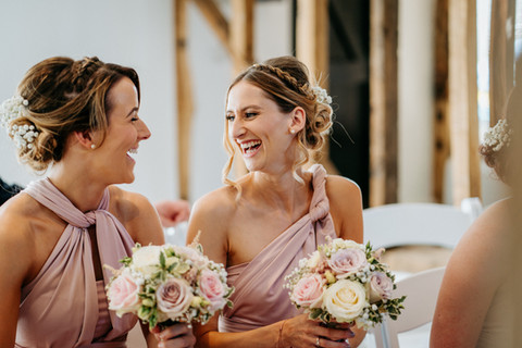 bridesmaids laughing with bouquets
