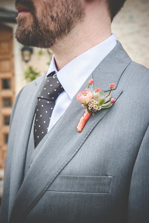 Boutonnière corail avec sa mini plante grasse assortie au bouquet de la mariée
