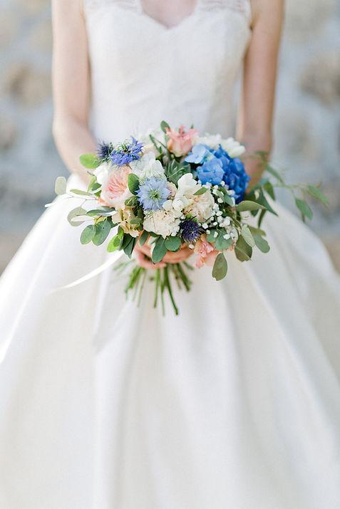 Un bouquet de mariée pétillant et pastel bleu et pêche, avec des nigelles et des chardons