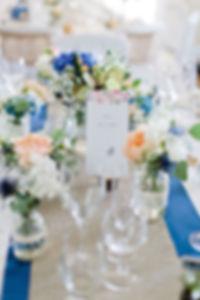 Table de mariage fleurie sur le thème campagne chic vintage, la dentelle et les bocaux font de jolis rappel du thème