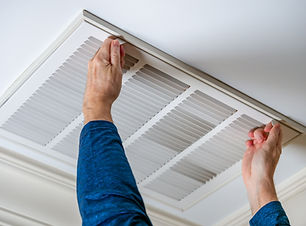 Man opening ceiling air vent to replace
