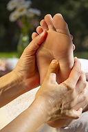 Hands of a reflexologist given a foot ma