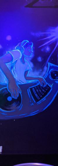DJ mural under a black light