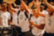 Quatro universitários vestino camisetas brancas da competição FSAE BR 2019. Todo estão aplaudindo, sorrindo, levantando as mãos. Estão felizes com o resultado da competição de Fórmula Estudantil