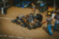 Carro de Fórmula SAE sendo levado do boxes da cometição para a inspeção. Há uma pessoa guiando o carro, enquanto duas o empurram utilizando a push bar. Há também uma pessoa acompanhando o crro ao seu lado. Ao fundo, vê-se um box de outra equipe.