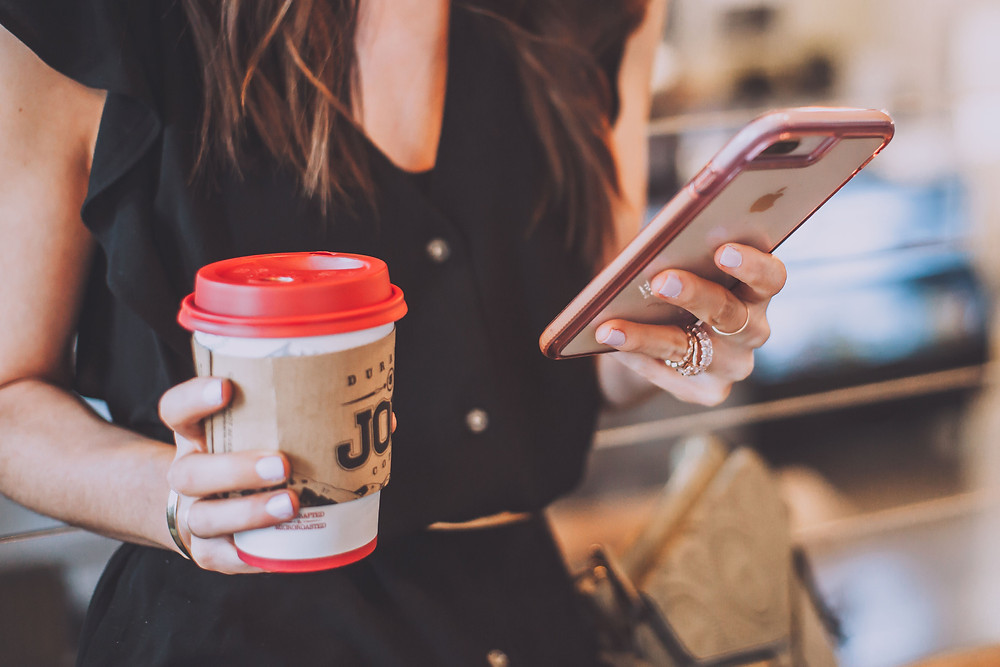 women holding coffee and cell phone