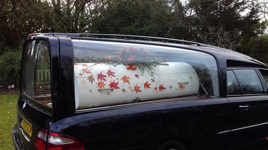 Holly's Funerals bespoke hand painted coffin in hearse