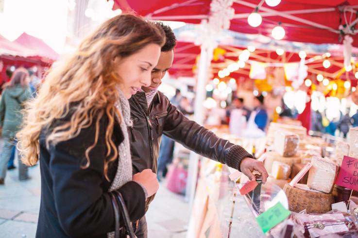 Paare, die am Käse Mit Blick auf Markt