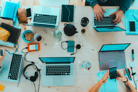 A group of coworkers gathers at a table with food, laptops, and mobile devices to take notes as they plan a marketing strategy for a business